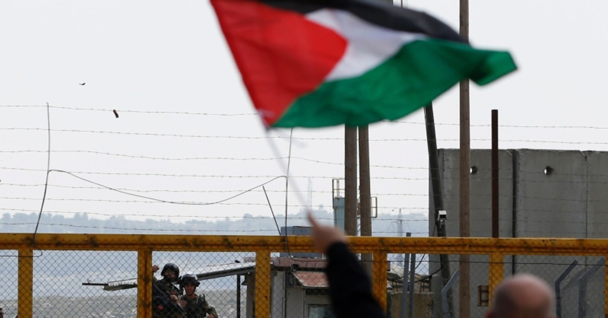 A Palestinian protester waves his national flag in front of Israeli security forces as they mark Land Day outside the compound of the Israeli-run Ofer prison near Betunia in the Israeli occupied West Bank on March 30, 2016. (AFP Photo)
