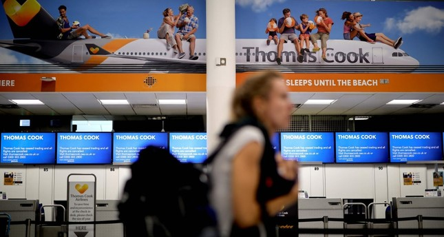 Passengers walk past the closed Thomas Cook check-in desks at the South Terminal of London Gatwick Airport in Crawley, south of London, Sept. 23, 2019,