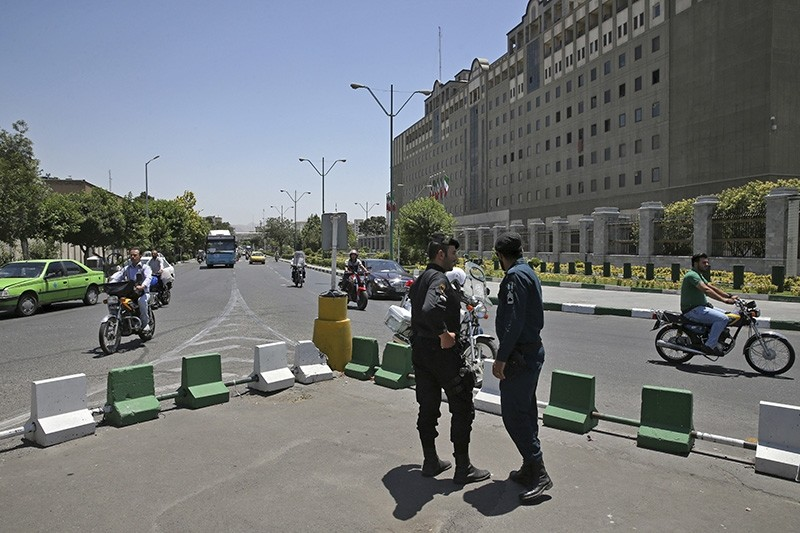 Police officers stand guard as vehicles drive past Iran's parliament building in Tehran, Iran (AP File Photo)