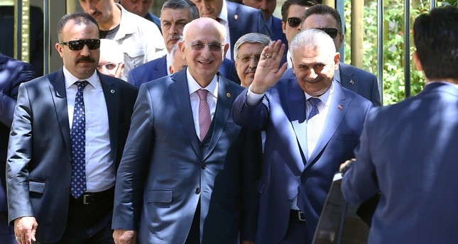 Prime minister Binali Yıldırım waves to cameras as he leaves the Parliament alongside Speaker Ismail Kahraman (L), in Ankara, on July 3, 2018. (AA Photo)