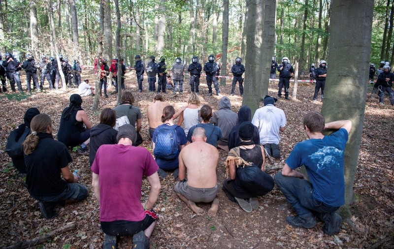 Activists kneel after a man fell off a tree house at the Hambach forest in Kerpen, Germany, Wednesday, Sept. 19, 2018. (AP Photo)
