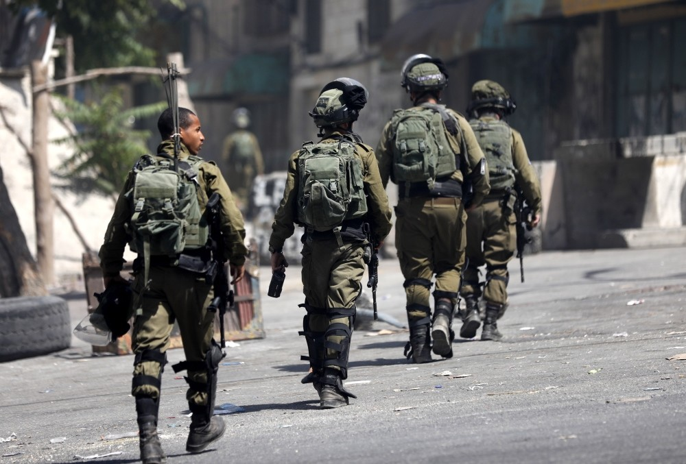 Israeli soldiers take position during clashes with Palestinians, West Bank, July 27.