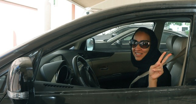 Saudi activist Manal Al Sharif flashes the sign for victory as she drives her car in the Gulf Emirate city on October 22, 2013. (AFP Photo)