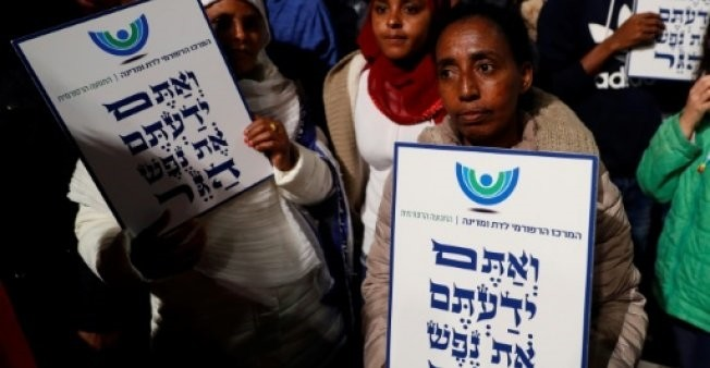 African migrants hold signs Hebrew signs: ,You come from the Bible, you too are refugees,, during a demonstration in Tel Aviv (AFP File Photo)