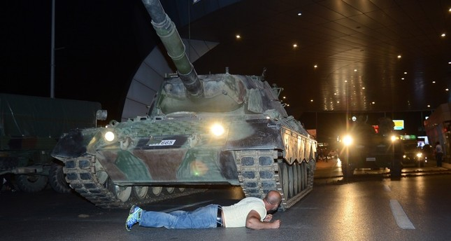Metin Doğan, one of the civilians who went to the airport to confront the putschists, lies down in front of a tank commanded by the putschists at the airport, July 15, 2016.