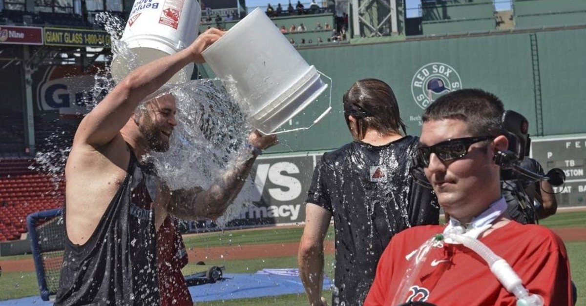 Boston Red Sox player Mike Napoli takes part in the re-launch of the Ice Bucket Challenge as former Boston College baseball player Pete Frates, right, looks on at Fenway Park in Boston, July 31, 2015. (AP Photo)
