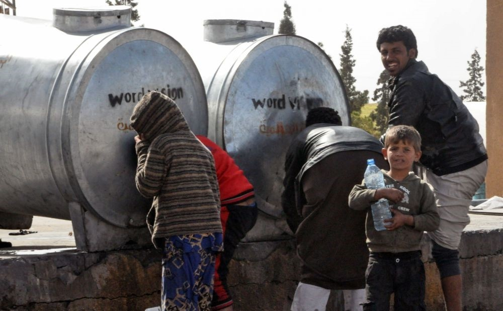 Displaced Syrians, who fled the countryside surrounding Daesh stronghold areas, are drawing water from tanks at a temporary camp in the village of Ain Issa, April 6. (AFP Photo)