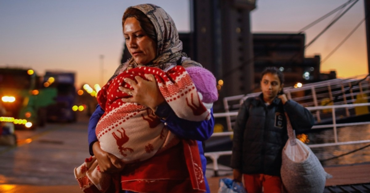 Refugees and migrants wait with their belongings after disembarking from a ferry at the port of Piraeus, near Athens, Tuesday, Oct. 1, 2019 (AP Photo)
