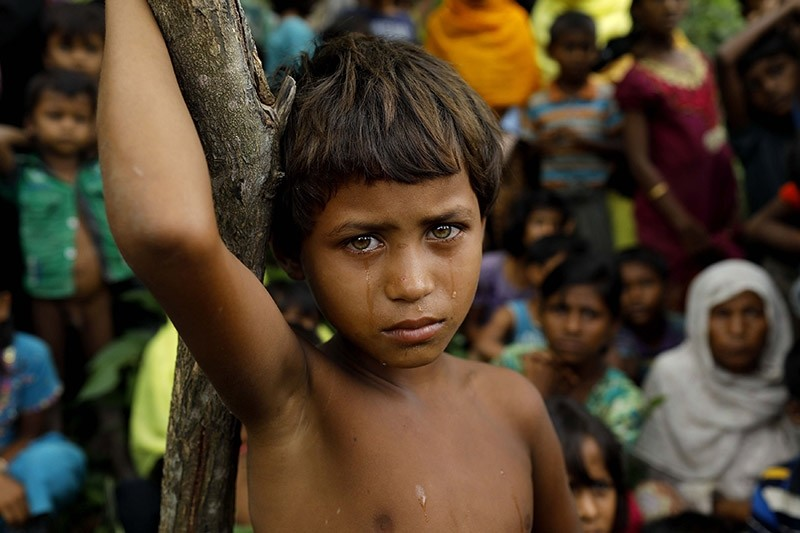 A Rohingya refugee girl looks next to newly arrived refugees who fled to Bangladesh from Myanmar in Ukhiya on September 6, 2017. (AFP Photo)