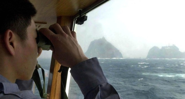 In this April 28, 2005, file photo, a South Korean coast guard looks at Dokdo islets, known as Takeshima in Japanese, through a telescope on the patrol ship Sambong-ho on the East Sea, South Korea. (AP Photo)