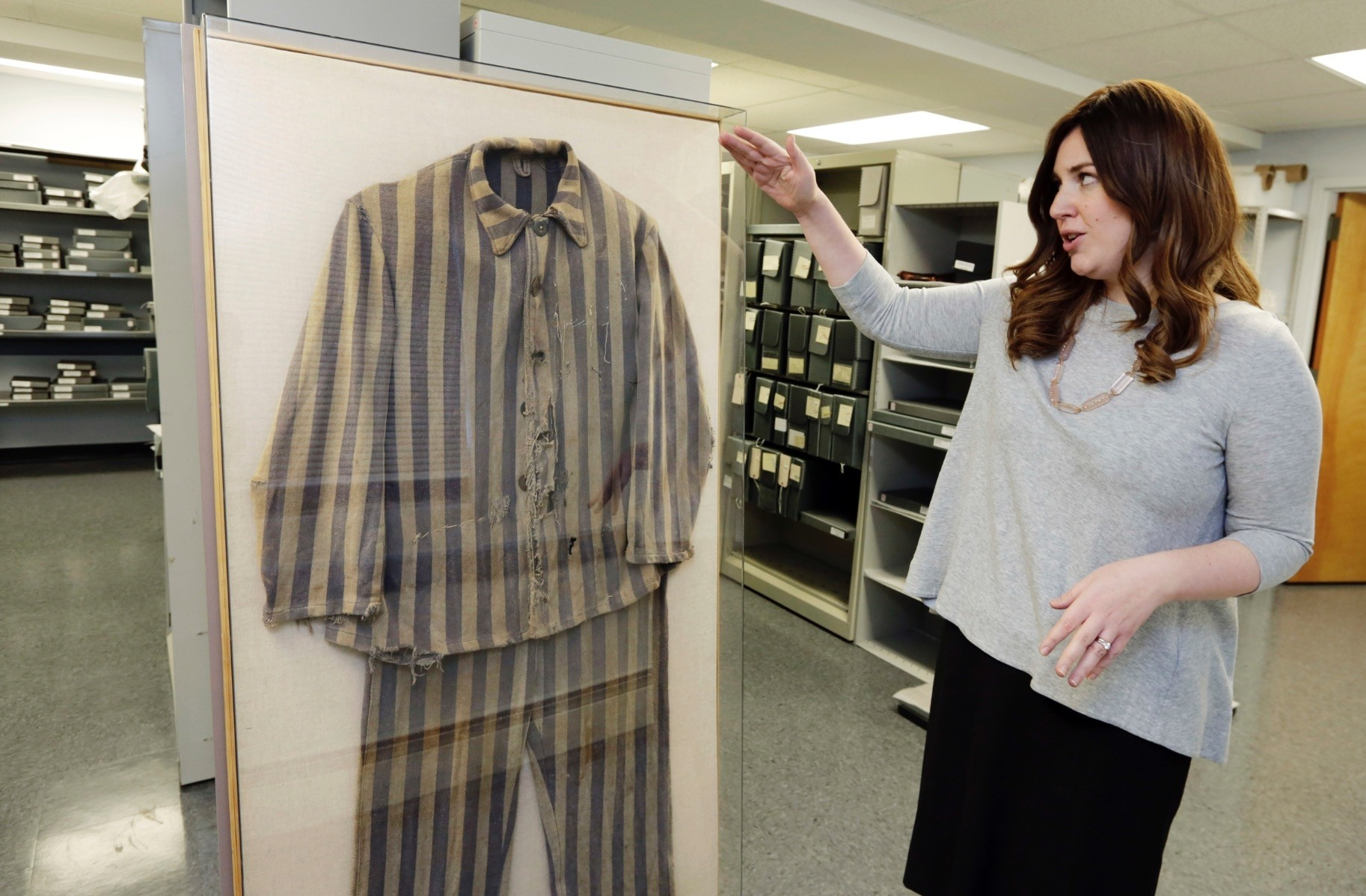 Director of Collections Shoshana Greenwald at the Amud Aish Memorial Museum in Brooklyn, N.Y., talks about the 1945 uniform from Bergen-Belsen concentration camp survivor Chaim Schmidt.