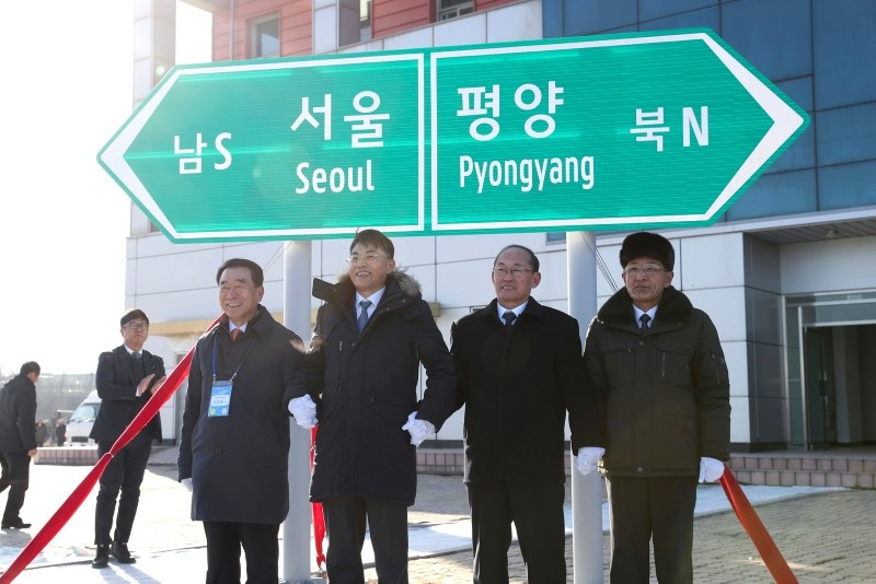 South and North Korean government officials pose in front of a signboard showing both capitals Pyongyang and Seoul during a groundbreaking ceremony at the Panmun Station in Kaesong, North Korea, Dec. 26, 2018. (AP Photo)