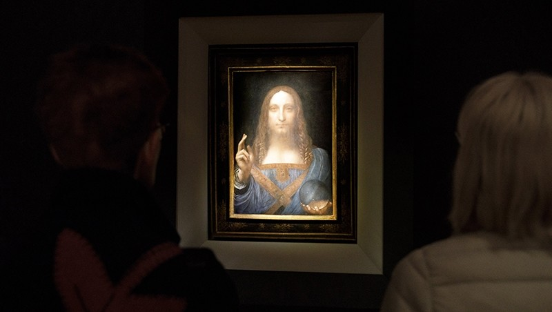 People look at the painting 'Salvator Mundi' by Leonardo da Vinci (circa 1500) during a public preview before an auctioning (EPA Photo)
