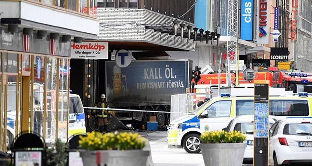 This file photo taken on April 7, 2017 shows emergency services members working at the scene where a truck crashed into the Ahlens department store at Drottninggatan in central Stockholm, April 7, 2017. (AFP Photo)