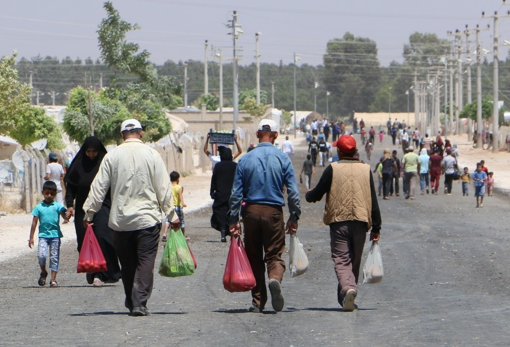 Syrian men carrying grocery bags return to their tents in the refugee camp in Aku00e7akale after traditional Eid shopping.