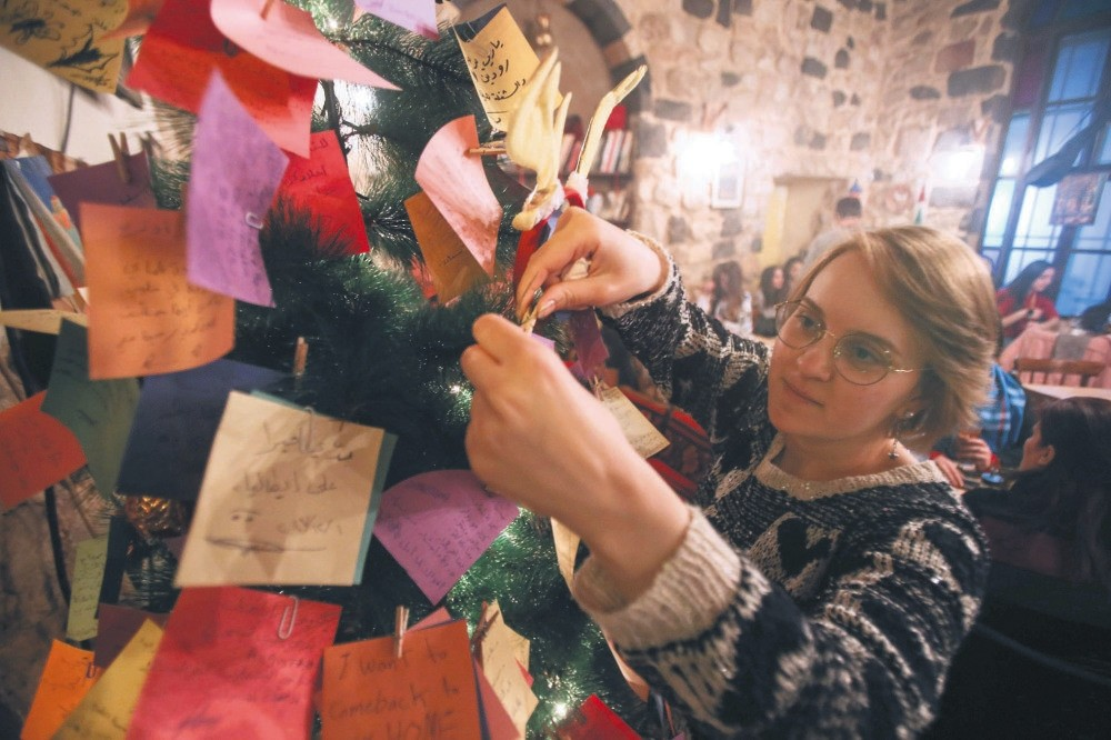 A Syrian youth hangs New Year wishes written on a card on a Christmas tree in the Zeriab coffee shop in the Syrian capital Damascus.