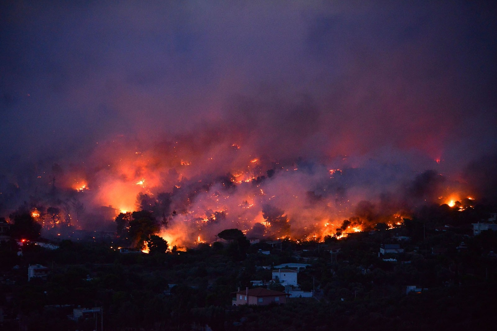 Flames rise as a wildfire burns in the town of Rafina, near Athens, July 23, 2018.