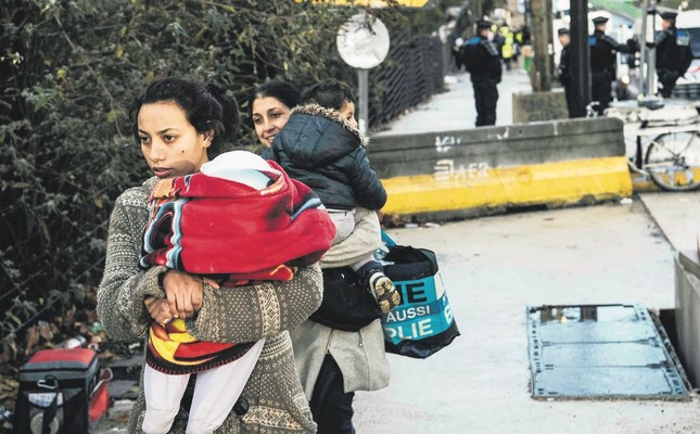 Roma women carry children during their evacuation by police from a makeshift camp, Paris, Nov. 28.