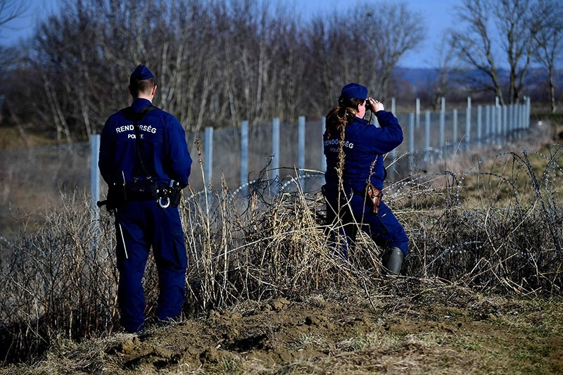 This photo taken on February 23, 2017 shows local police officials patrolling in front of part of the border fence on the Hungarian-Croatian border (Reuters Photo)