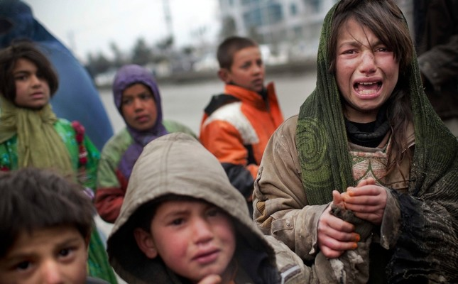 An Afghan refugee girl reacts after another child stole her food voucher while she was queuing in front a truck organized by the World Food Program in Kabul (AP Photo)