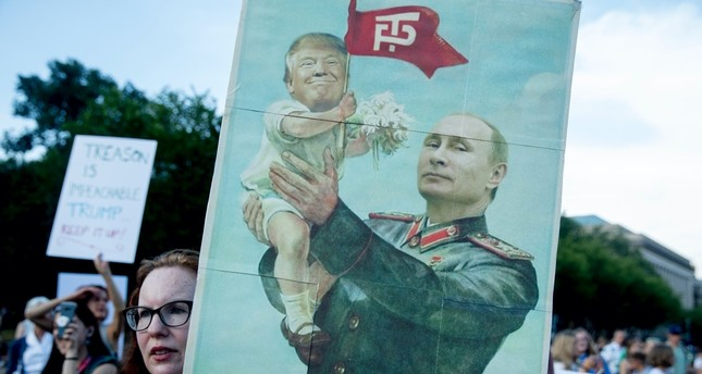 A woman holds a sign satirizing Russian President Vladimir Putin and U.S. President Donald Trump during a protest outside the White House, July 17.