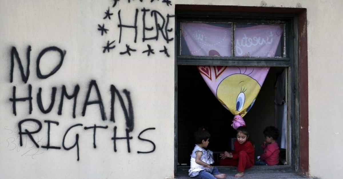 Children sit on a window sill at a makeshift camp for refugees and migrants, Idomeni, Greece, May 19, 2019. (REUTERS Photo)MAY 19, 2016. REUTERS/Kostas Tsironis TPX IMAGES OF THE DAY