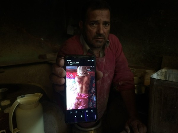 In this Monday, Aug. 26, 2019, photo, a Kashmiri baker Sonaullah Sofi displays a photograph of his son after he was allegedly tortured by Indian army soldiers at their bakery in the southern village of Parigam, Indian controlled Kashmir. (AP Photo)