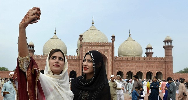 Pakistani women take selfie photographs after offering Eid al-Fitr prayers at the Badshahi Masjid in Lahore on July 6, 2016. (AFP Photo)