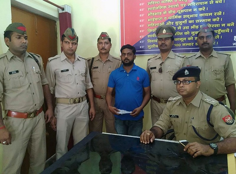 Ram Chandra (C), who has been accused of murder, looks on surrounded by policemen at a police station in Lakhimpur Kheri district in India's northern Uttar Pradesh state on May 1, 2018 (AFP Photo)