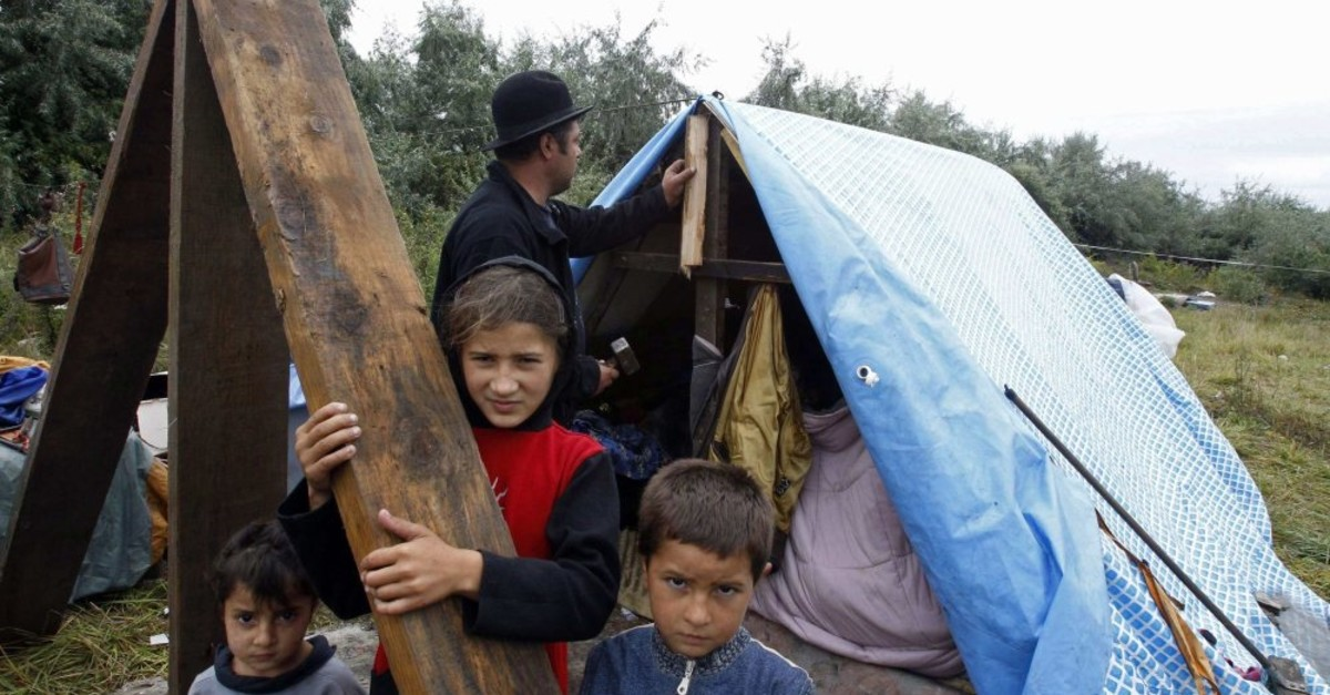 A Roma family stands outside their makeshift shelter, Roubaix, Aug. 17, 2010.