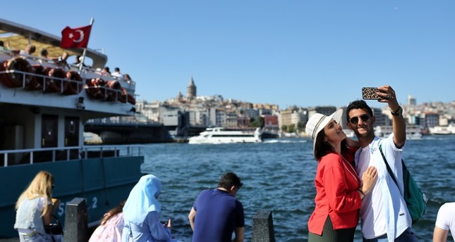 A couple takes a picture in front of the Galata Tower overlooking the Golden Horn in Istanbul, July 2, 2019. AA Photo