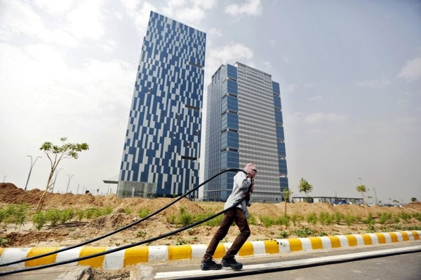 A laborer pulls a cable in front of two office buildings in Gujarat International Finance Tec-City (GIFT) at Gandhinagar, in the western Indian state of Gujarat.