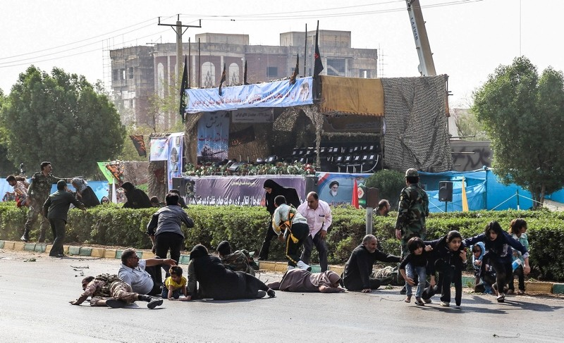 This picture taken on September 22, 2018 in the southwestern Iranian city of Ahvaz shows Iranian men, women, and children, lying on ground and some seeking cover at the scene of an attack on a military parade. (AFP Photo)