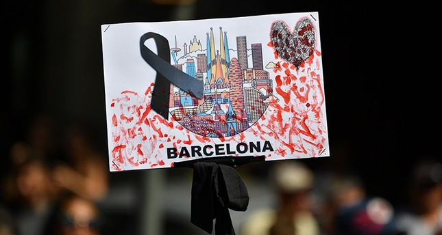 A placard with black ribbon is brandished before observing a minute of silence for victims of attack at Plaza de Catalunya on Aug. 18, 2017, day after van plowed into crowd, killing 13 people and injuring over 100 in Barcelona, Spain. (AFP Photo)