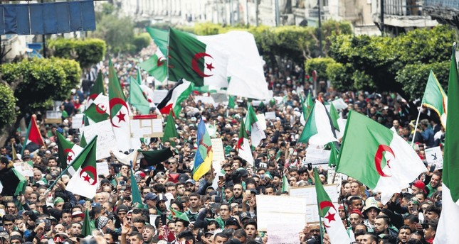 Demonstrators hold flags and banners as they return to the streets to press demands for wholesale democratic change well beyond former President Abdelaziz Bouteflika's resignation, in Algiers, Algeria, April 19, 2019.