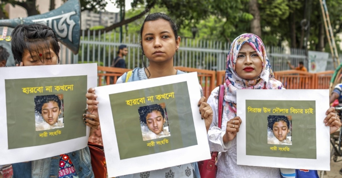 In this photo taken on April 12, 2019 Bangladeshi women hold placards and photographs of schoolgirl Nusrat Jahan Rafi at a protest in Dhaka, following her murder by being set on fire after she had reported a sexual assault. (AFP Photo)