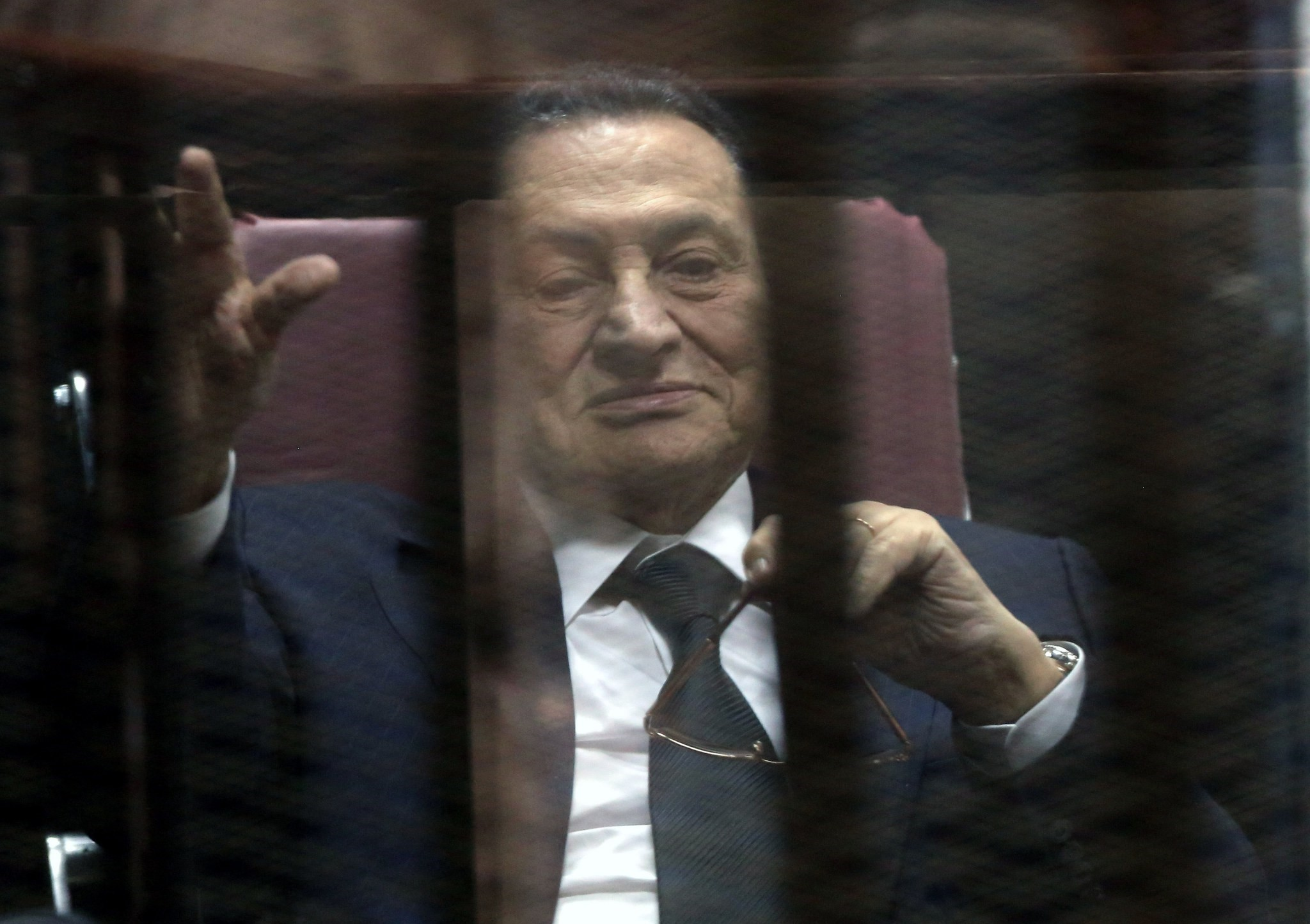 Former Egyptian President Hosni Mubarak waves from defendants' cage at a courtroom during his trial in Cairo, Egypt, 29 April 2015. (EPA Photo)