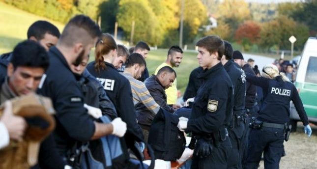 Migrants are controlled by German police officer near Breitenberg, south eastern Germany, October 5 (Reuters Photo)