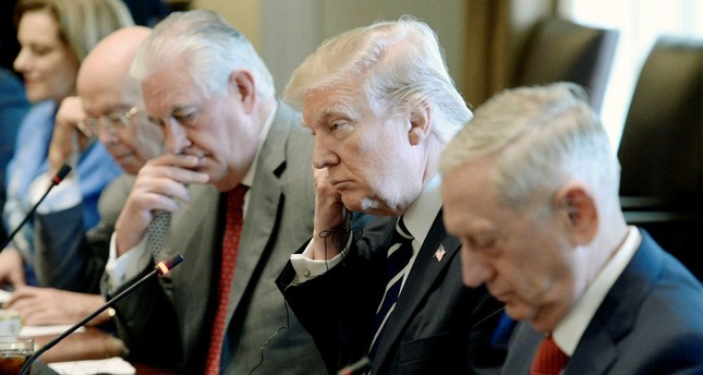U.S. President Donald J. Trump flanked by  Secretary of State Rex Tillerson (L) and  Defense Secretary Jim Mattis (R) in the Cabinet Room of the White House in Washington,  April 3.