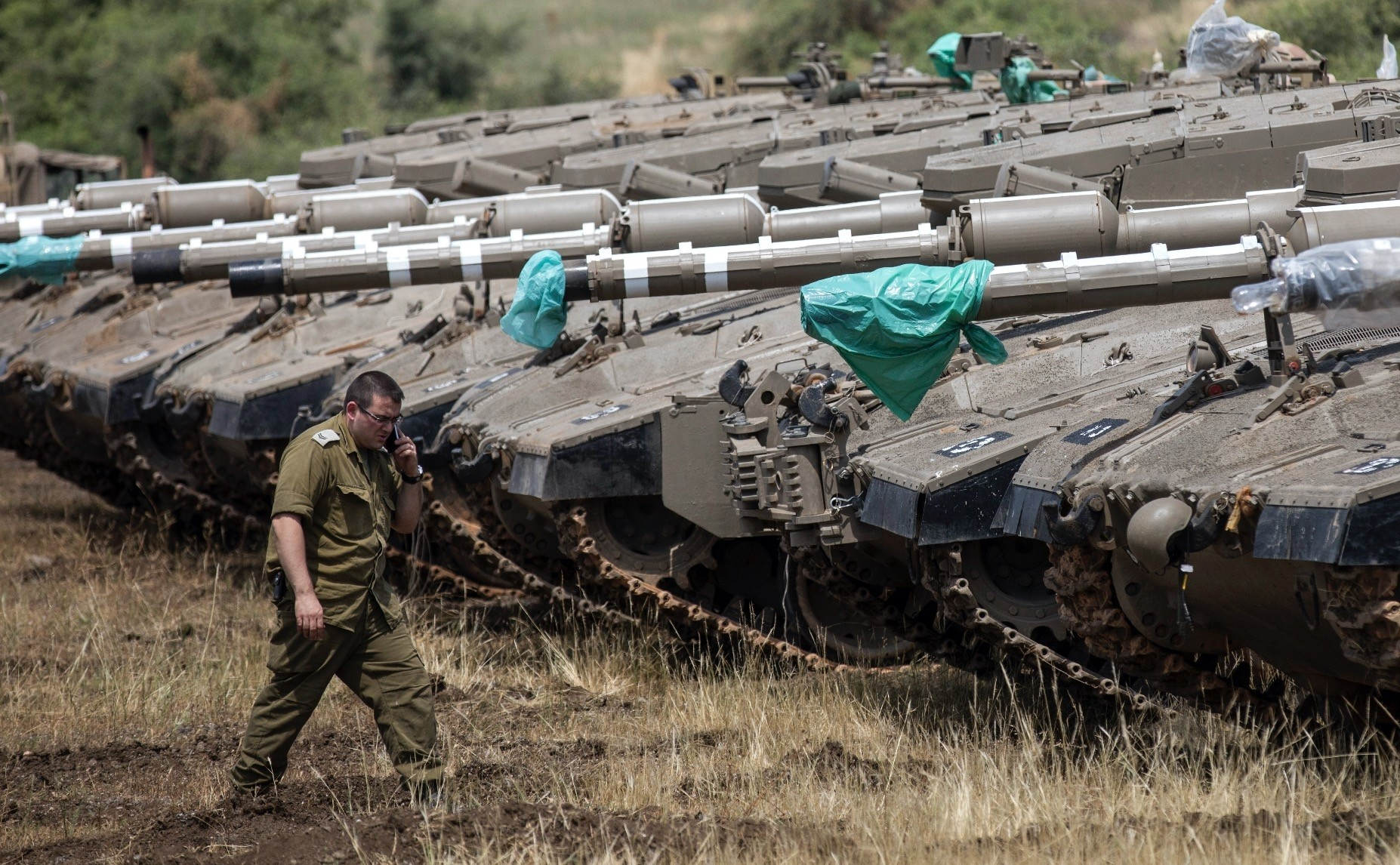An Israeli soldier walks next to Merkava tanks deployed near the Israeli-Syrian border, Golan Heights, May 9.