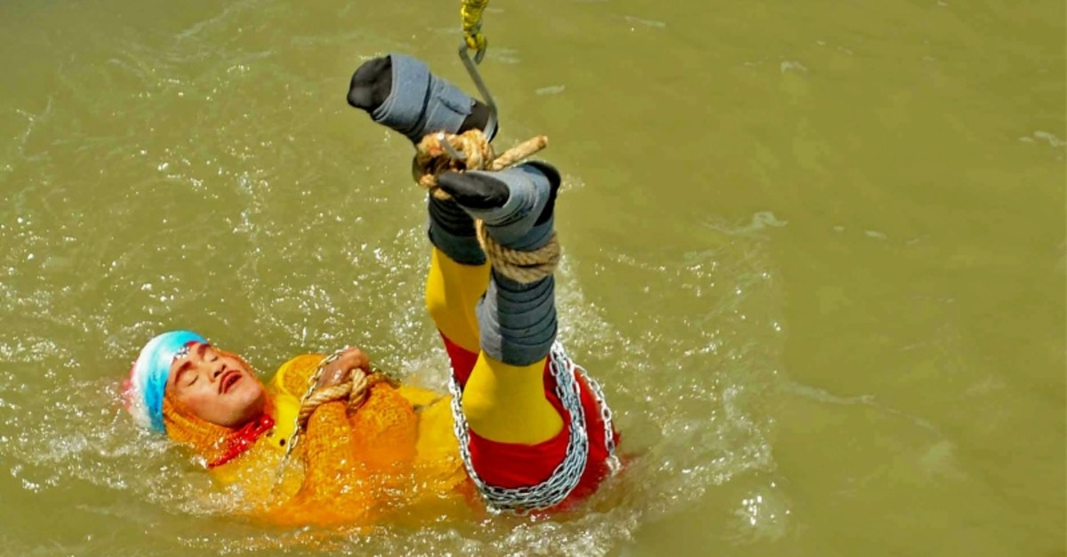 In this photo taken on June 16, 2019 Indian stuntman Chanchal Lahiri, known by his stage name ,Jadugar Mandrake,, is lowered into the Ganges river, while tied up with steel chains and ropes, in Kolkata. (AFP Photo)