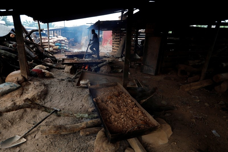 Gold ore is roasted on a fire at the unlicensed mining site of Nsuaem Top in Ghana, November 24, 2018.