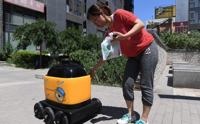 A woman picks up groceries delivered by a Zhen Robotics delivery robot at a residential compound during a demonstration in Beijing.