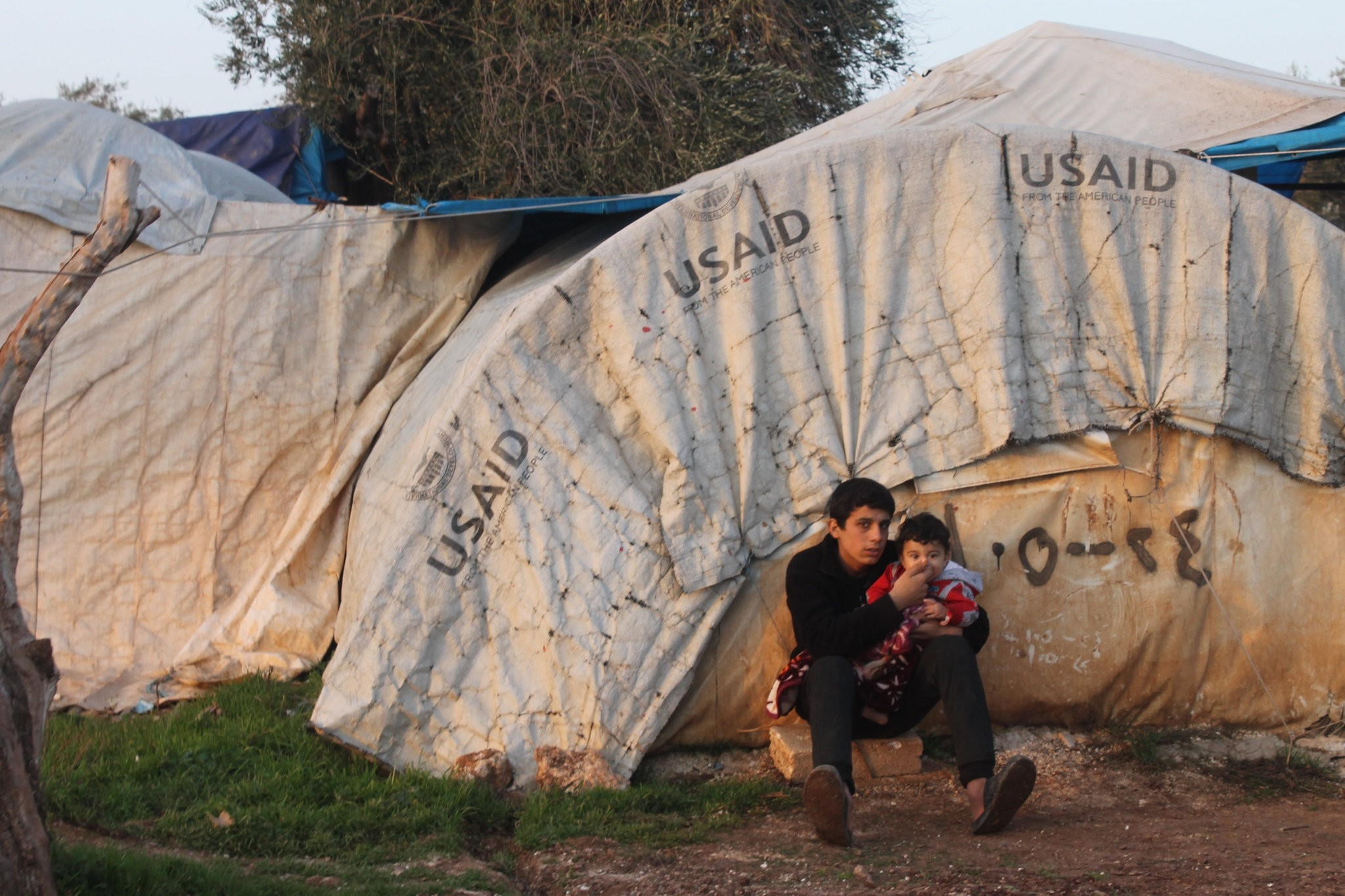 A Syrian teenager hugs his brother in front of their tent in the Atme Refugee Camp. A few days ago, a rocket fired by YPG terrorists hit the camp where Syrian refugees took refugee after fleeing terrorist attacks by in their hometowns.