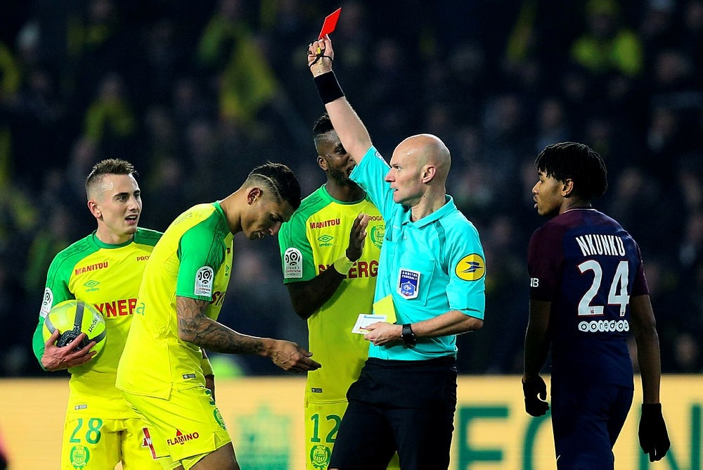 Referee Tony Chapron gives a red card to Nantes defender Diego Carlos, left, after Carlos inadvertently clipped the referee's heels during the French League One soccer match between Nantes and Paris Saint Germain. (AP Photo)