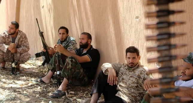 Fighters from forces aligned with Libya's new unity government rest after clearing the Zaafran area in Sirte.