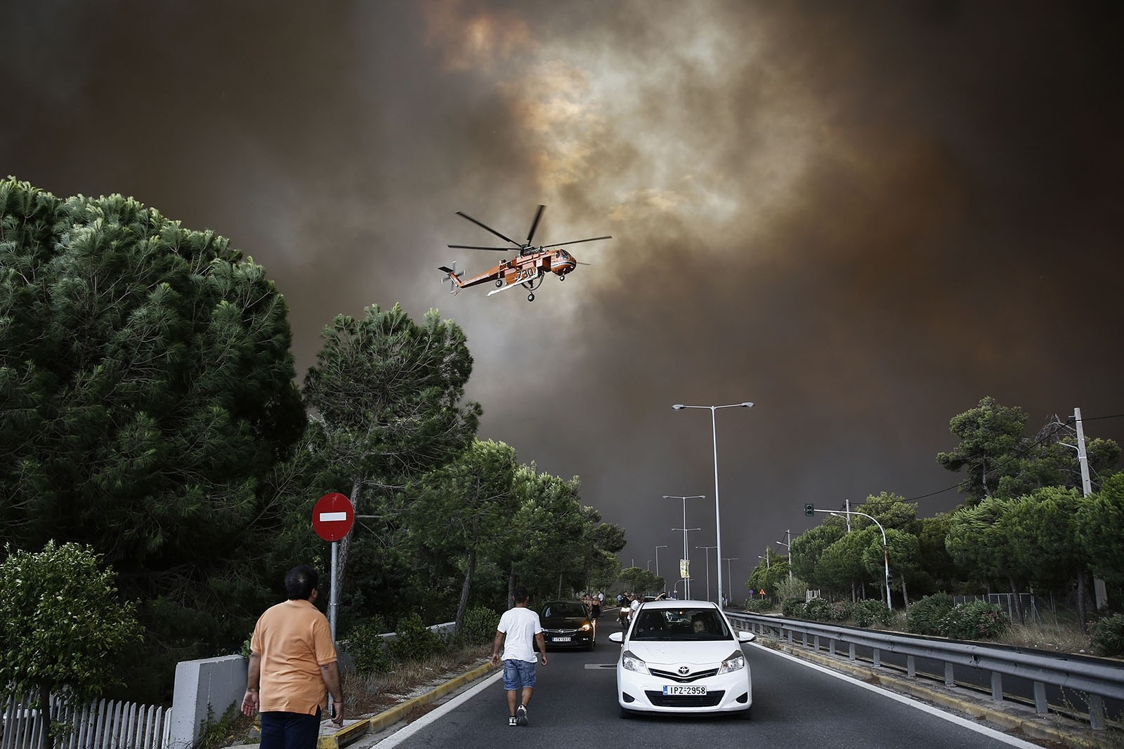 A firefighting helicopter flies over an avenue during a forest fire in Neo Voutsa, a northeast suburb of Athens, Greece, July 23, 2018.