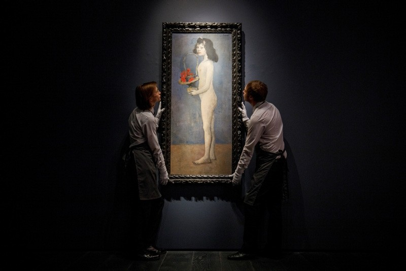 Gallery assistants pose with the painting 'Fillette a la corbeille fleurie' (Girl with flower basket) by Spanish artist Pablo Picasso during a photocall at Christie's auction house in London, Britain, 20 February 2018. (EPA Photo)