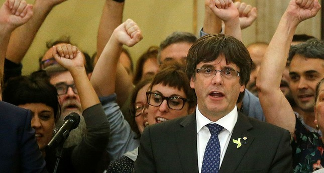 Catalan President Carles Puigdemont sings the Catalan anthem inside the parliament after a vote on independence in Barcelona, Spain. (AP Photo)