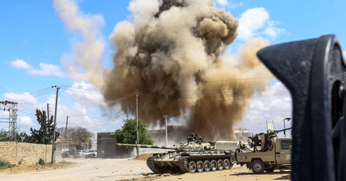 This picture taken on April 12, 2019, shows a smoke plume rising from an air strike behind a tank and technicals belonging to forces loyal to Libya's GNA, during clashes in the suburb of Wadi Rabie about 30 km south of  Tripoli. (AFP Photo)